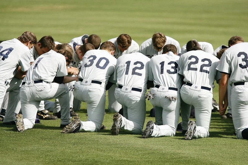 A baseball team kneeling to pray before a game
