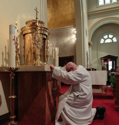A priest kneeling before the Blessed Sacrement
